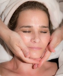 Axis AL esthetician applying facial moisturizer